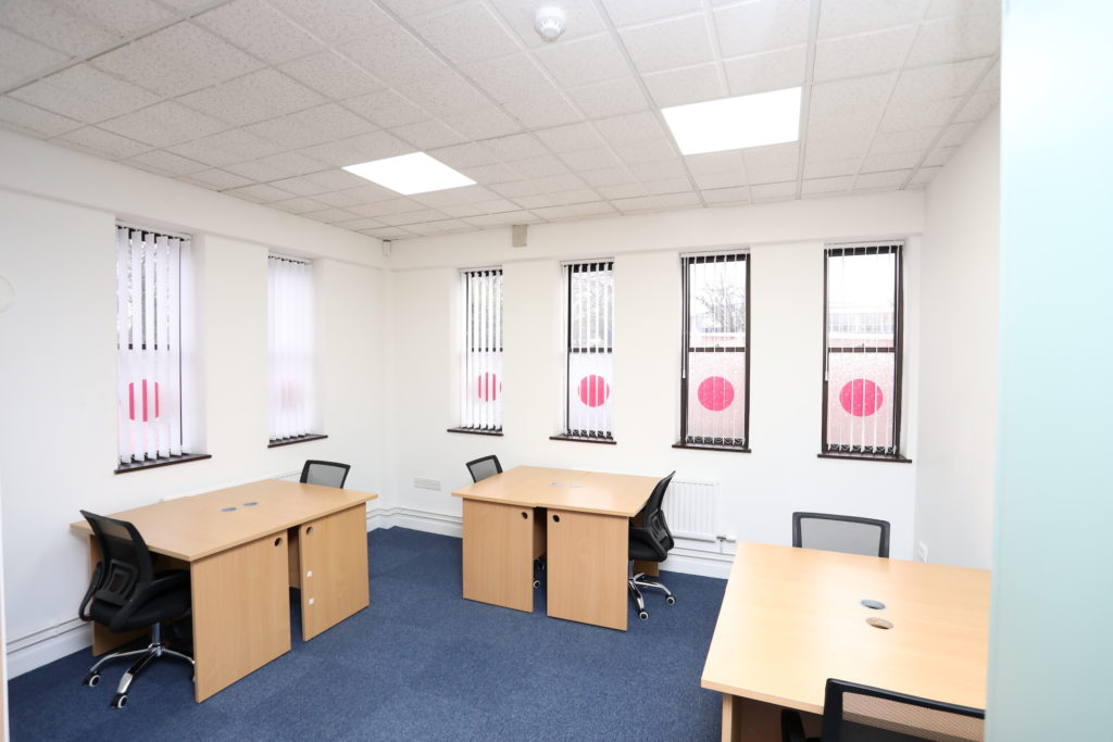 Co*Shabang Gateshead co-sharing work desk stations with beech desks and office chairs, white room with six windows, and blue carpet, Available for rent for Co-working, Co-sharing, hot desking, Office & Meetings Rooms.