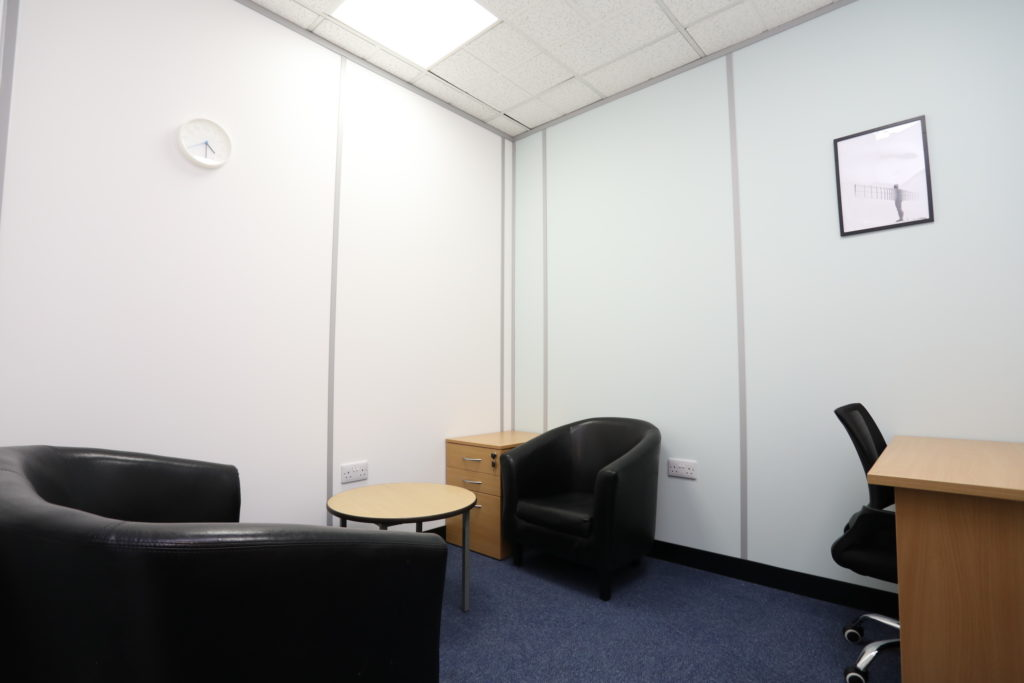 Co*Shabang Gateshead office space for rent with beech desk, coffee table and filing cabinet, black office chairs and two black bucket chairs, white room with blue carpet, Available for rent for Co-working, Co-sharing, hot desking, Office & Meetings Rooms.