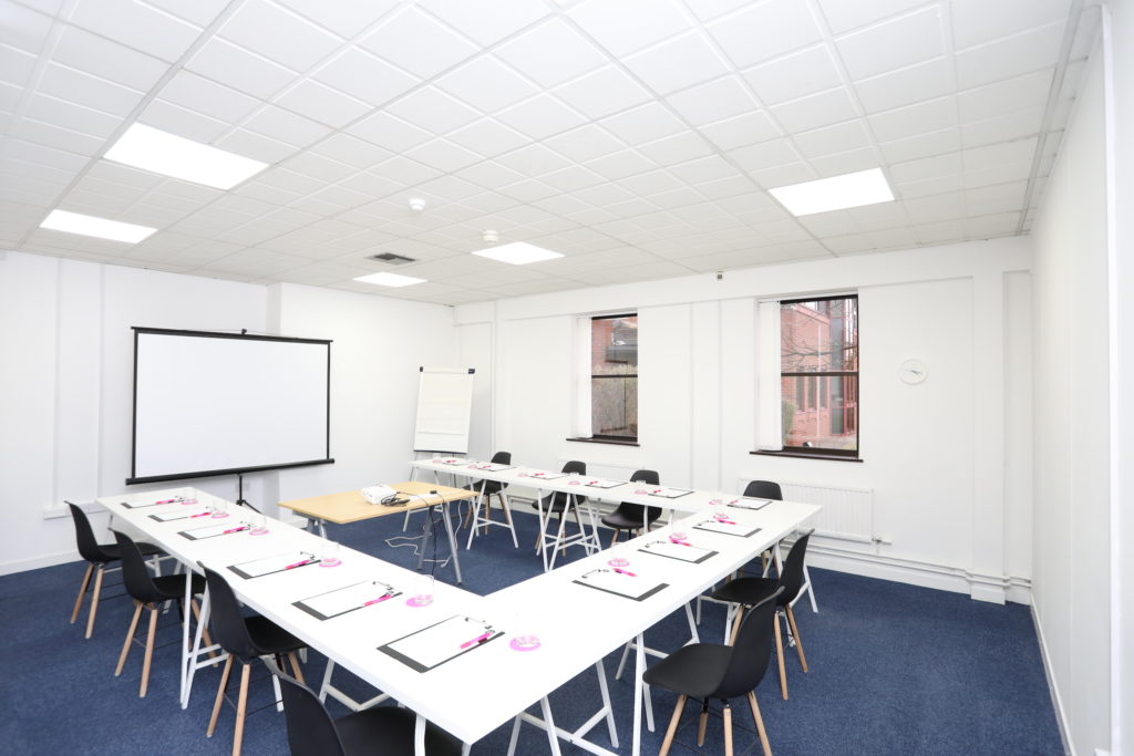 Co*Shabang Gateshead Meeting Rooms available, tables and chairs set out in a square with a projector screen, large white room with blue carpet and two windows available for Co-working, Co-sharing, Office & Meetings Rooms.