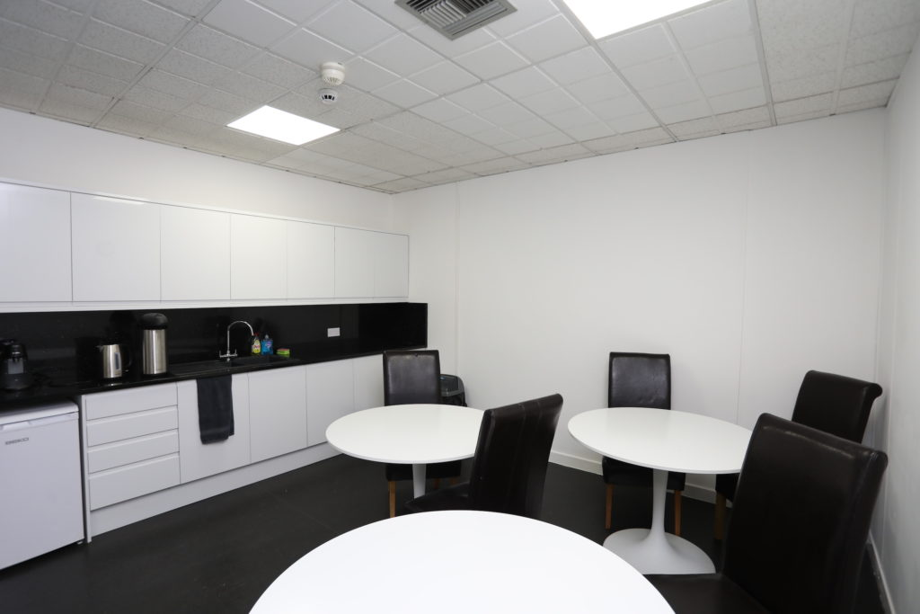 Co*Shabang Gateshead Offices Shared Kitchen and lunch area, white kitchen units and black chairs, available for Co-working, Co-sharing, Office & Meetings Rooms guests