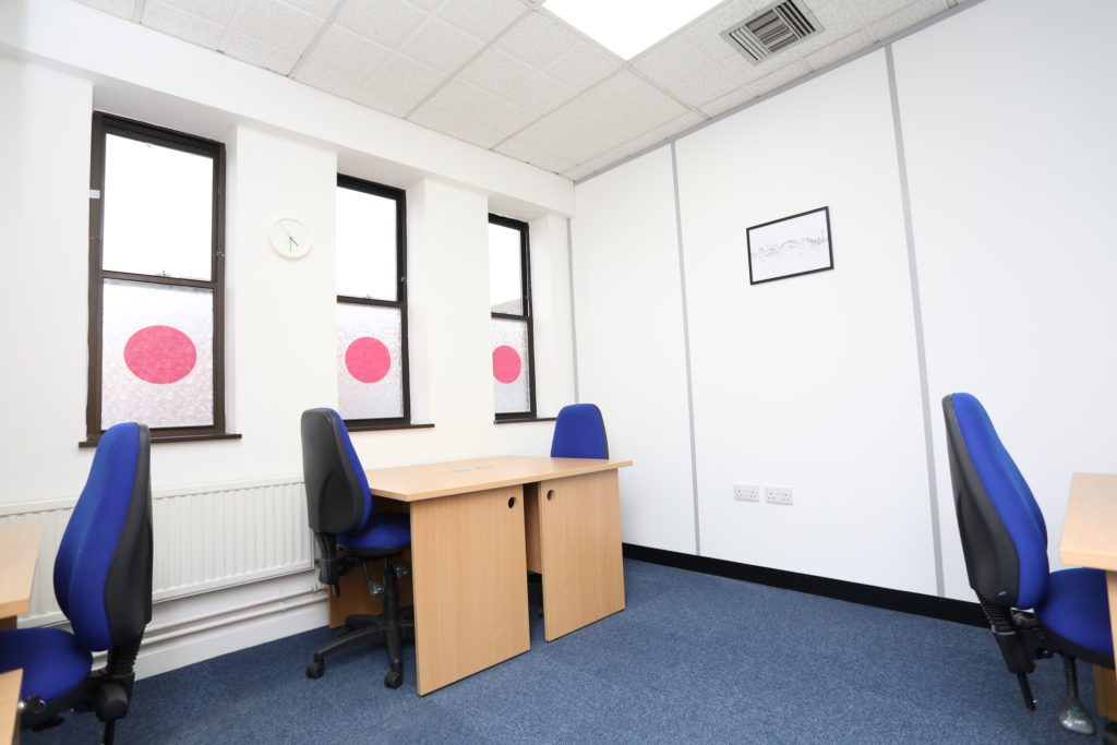 Co*Shabang Gateshead co-sharing work/desk stations with beech desks and office chairs, white room with three windows, and blue carpet, Available for rent for Co-working, Co-sharing, hot desking, Office & Meetings Rooms.